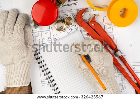 Mans hands in gloves writing in pad on draft background - stock photo