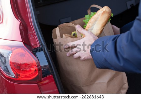 Mans hands loading a shopping bag in car trunk - stock photo