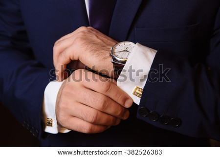 Mans hands with cufflinks and clocks. Elegant gentleman clother - stock photo