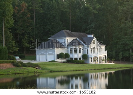 mansion by a lake, in a prestigious neighborhood - stock photo
