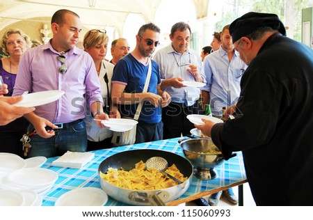 MANTOVA, ITALY - JUNE 13: People taste cherry and pumpkin hand made tortelli during Golosaria, fair show of food and gastronomy culture June 13, 2010 in Mantova, Italy. - stock photo