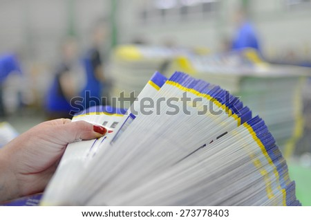 Manual control and count of printed material packets with blur workers at background - stock photo