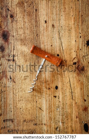 Manual corkscrew with a wooden handle and steel screw for opening bottles of wine lying centred on a textured wooden surface with copyspace - stock photo