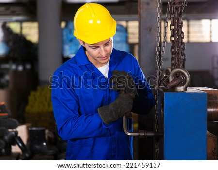 manual factory worker adjusting machine - stock photo