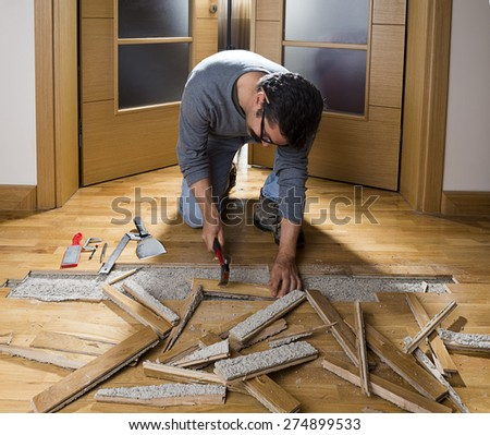 Manual worker disassembling wooden floor ruined from moisture and water leak - stock photo