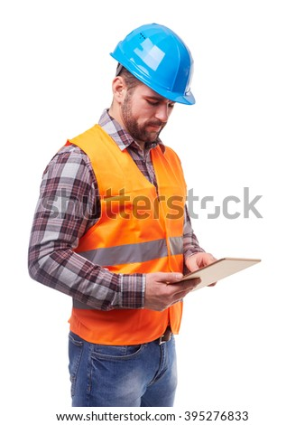 Manual worker in blue helmet and shirt using a digital tablet, isolated on white. - stock photo