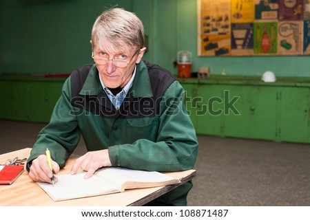 Manual worker male filling the journal in the workplace. Looking at camera - stock photo