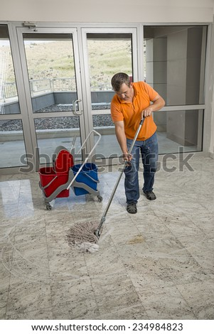 Manual worker mopping the floor.  - stock photo