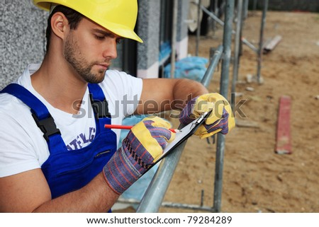 Manual worker on construction site writing on clipboard. - stock photo