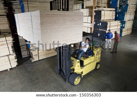 Manual worker operating a forklift truck in lumber industry - stock photo