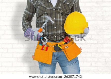 Manual worker wearing tool belt while holding hammer and helmet against white wall - stock photo