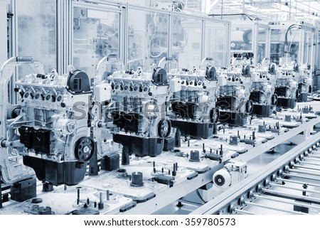 Manufactoring line with new engine parts. Photo is tone to cool blue color. Car factory. Car parts. Engine factory. New engine factory. Engines on line. - stock photo