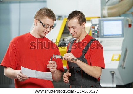 manufacture technician workers discussing and measure detail near cnc milling machine center at tool workshop - stock photo