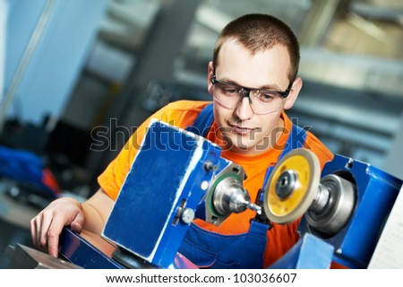 manufacture worker in uniform and protective glasses working on sharpening machine tool - stock photo