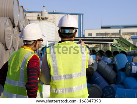 Manufacture workers checking drums - stock photo