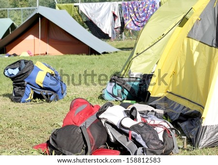 many backpacks of hikers in the midst of camping tents - stock photo