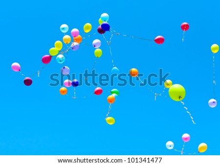 Many balloons fly into the blue sky - stock photo