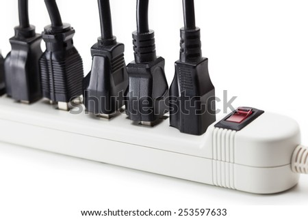Many black electrical plugs connected to a power strip or extension block. Isolated on white. - stock photo