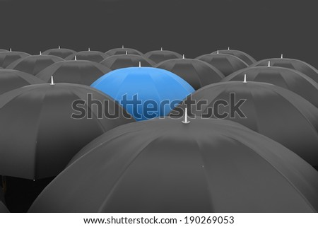Many black umbrellas. One blue unique umbrella - stock photo