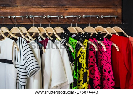 Many blouses on hangers in the dressing room. - stock photo