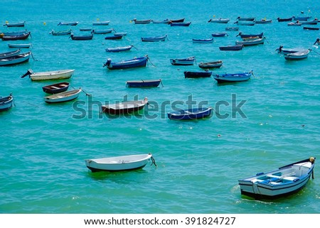 Many boats in a dock, harbor on clear blue water. Fishing village in Mediterranean sea, Spain, Europe. Refugees boat floating on the sea. Beautiful nature and travel background. - stock photo