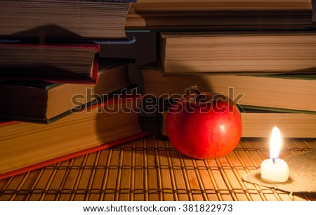 Many books by candlelight - stock photo