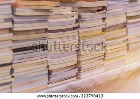 Many books pile on wooden table at library. - stock photo