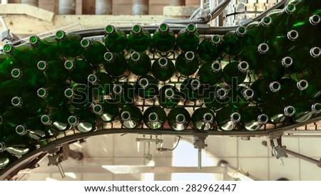 Many bottles on conveyor belt in factory - stock photo