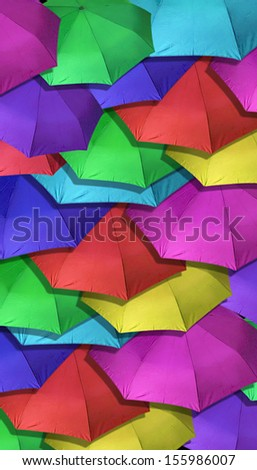 Many Brightly Colored Umbrellas overlapping each other for background - stock photo