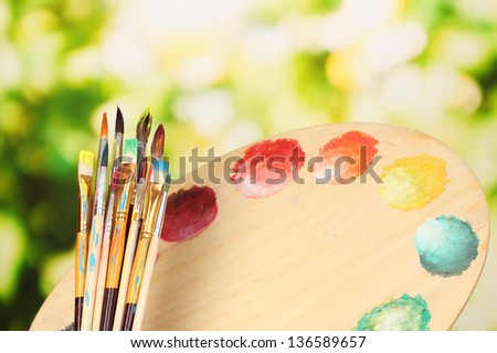 Many brush in paint on nature background - stock photo