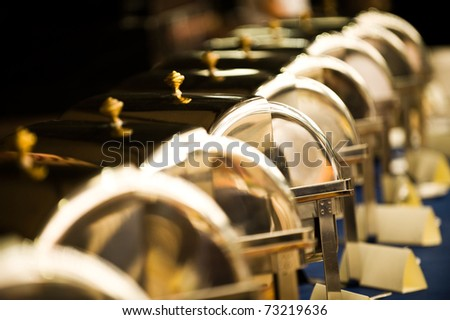 Many buffet heated trays ready for service, blue tone. - stock photo