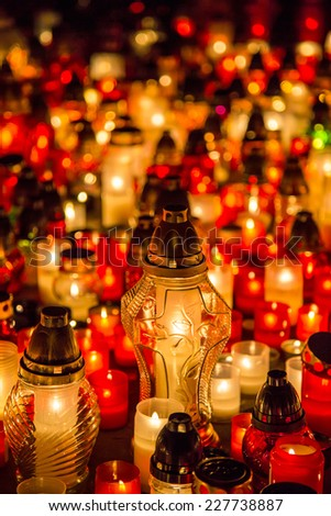 Many burning candles in the cemetery at night on the occasion memory of the deceased.Souls. - stock photo