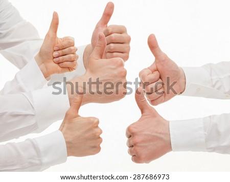 Many business people showing  thumb up signs on white background - stock photo