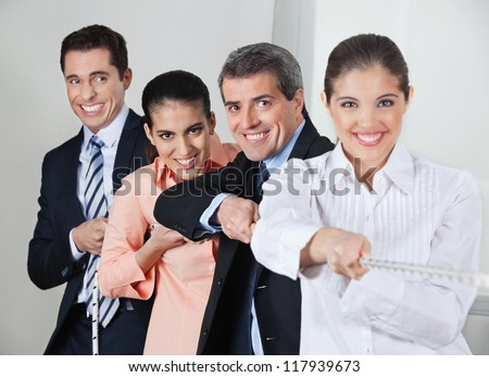 Many businesspeople acting in concert while pulling on a string - stock photo