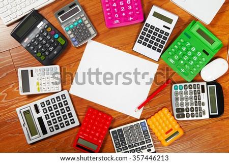 Many calculators lying on the wooden flooring - stock photo