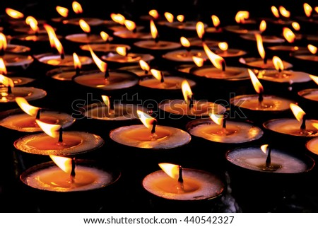 Many candle flames glowing in the dark, create a spiritual atmosphere. - stock photo