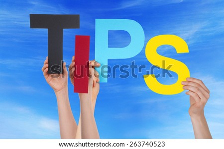 Many Caucasian People And Hands Holding Colorful  Letters Or Characters Building The English Word Tips On Blue Sky - stock photo