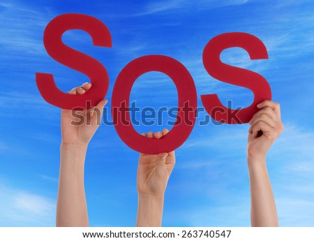 Many Caucasian People And Hands Holding Red Letters Or Characters Building The English Word Sos On Blue Sky - stock photo