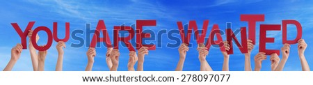 Many Caucasian People And Hands Holding Red Letters Or Characters Building The English Word You Are Wanted On Blue Sky - stock photo
