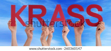 Many Caucasian People And Hands Holding Red Straight Letters Or Characters Building The German Word Krass Which Means Cool On Blue Sky - stock photo