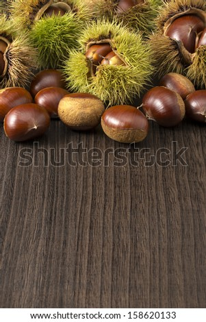 many chestnuts with husk on dark wooden table - stock photo
