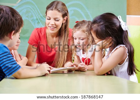 Many children at table reading a book with kindergarten teacher in preschool - stock photo