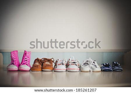 many children's shoes standing in a row on the table - stock photo