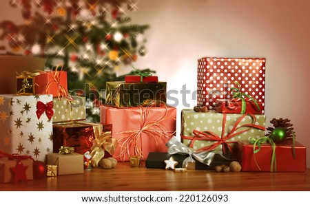 many Christmas presents on a table in the background a Christmas tree - stock photo