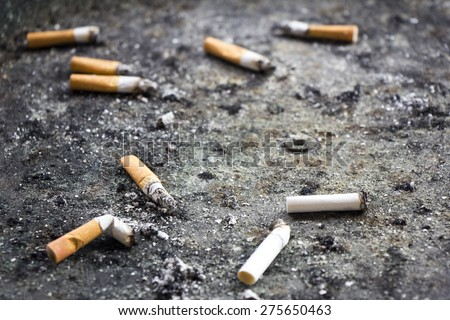 Many Cigarette butts in the dirty ashtray. - stock photo