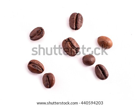 Many coffee beans in the background. Texture of the coffee beans on a white background. Smelly, saturated brown arabic coffee beans - stock photo
