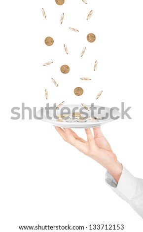 Many coins falling on kitchen plate on male hand isolated on white - stock photo