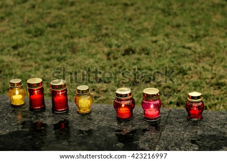 many colorful candles with light burning in city center on marble stone, memorial day and sad bereavement moment - stock photo
