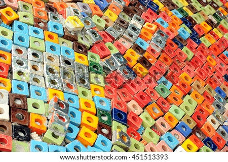 many colorful ceramic cube art blocks with circle hole at public park, Ratchaburi, Thailand. Focusing to right side of photo, unfocused others feel like background and texture on large wall. - stock photo