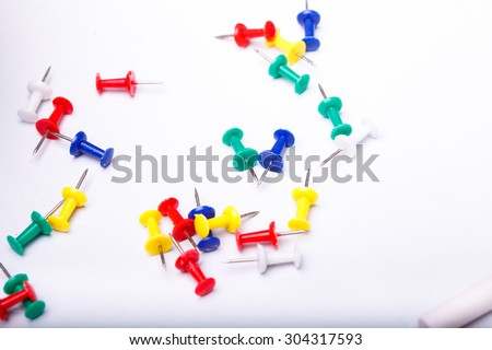 Many colorful drawing-pins of red yellow green blue lying on white school desk background copyspace, horizontal photo - stock photo